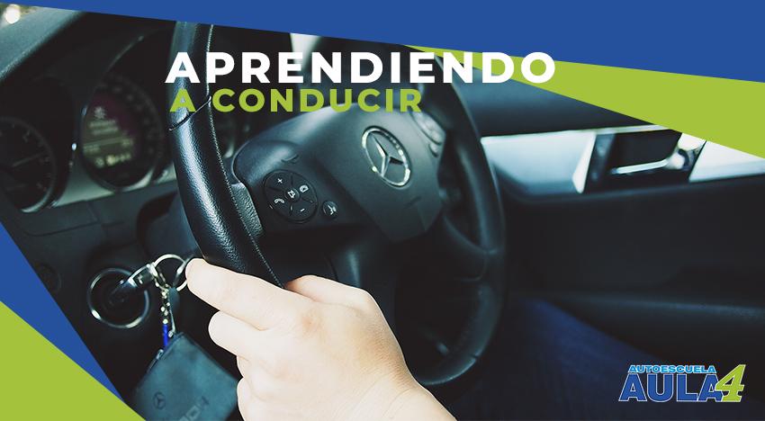 una persona con las manos en el volante de un coche
