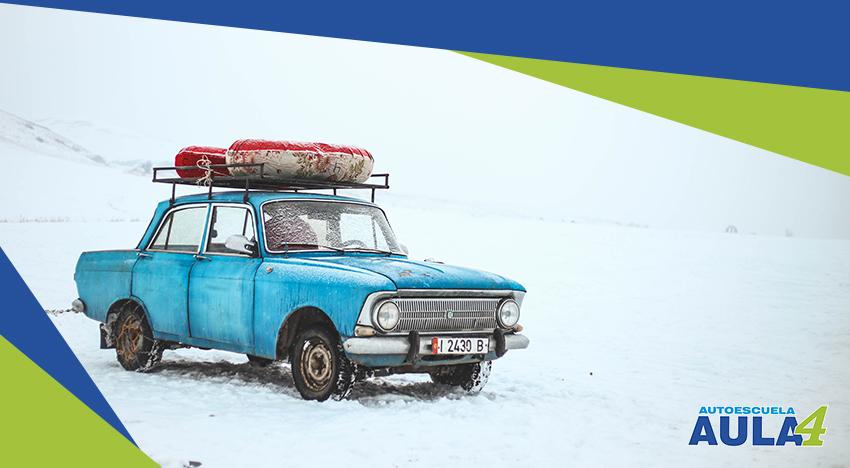 Coche circulando por una carretera nevada