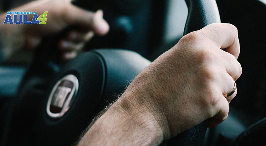Imagen de unas manos de una persona agarrando un volante del coche
